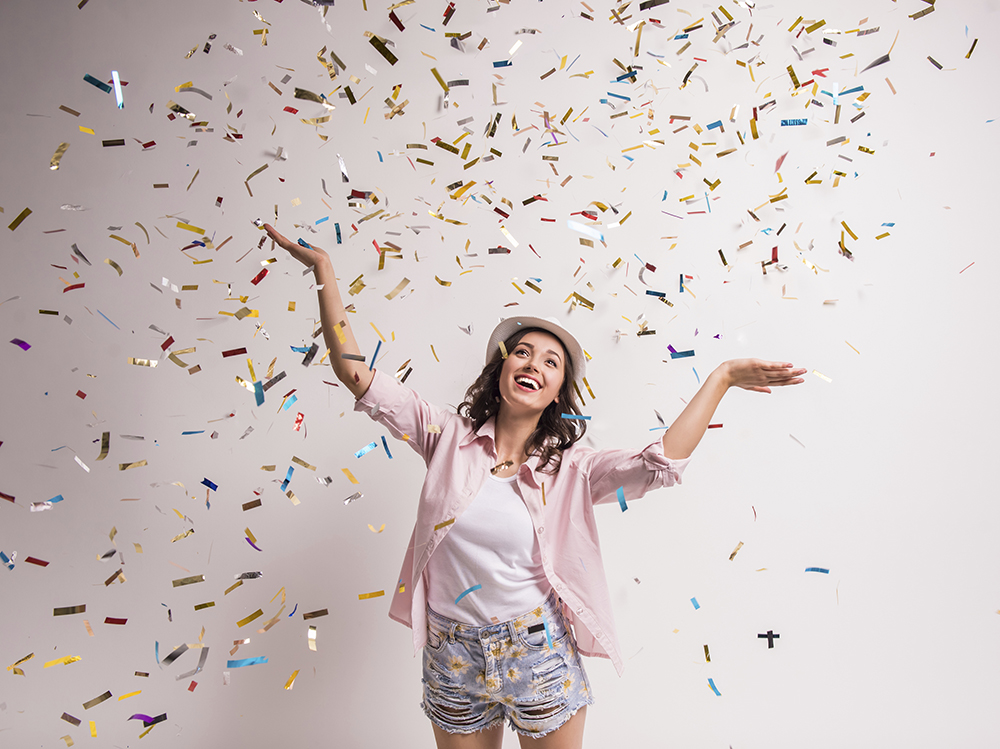 A young women throwing up confetti in celebration of Free CO-OP ATMs