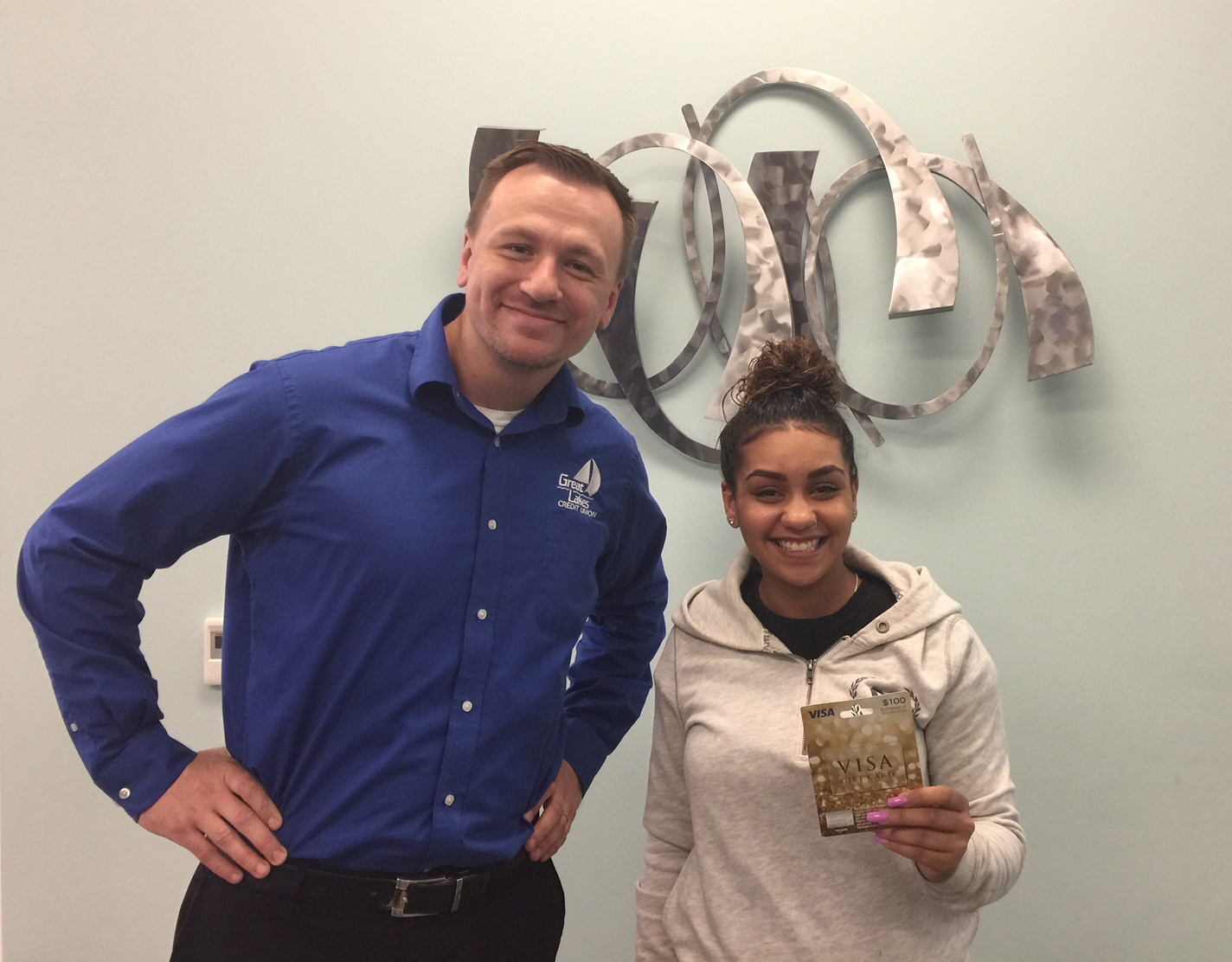 Youth savings month winner holding up her VISA gift card