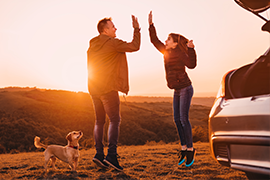 Young couple jumping in the air in-front of their new car