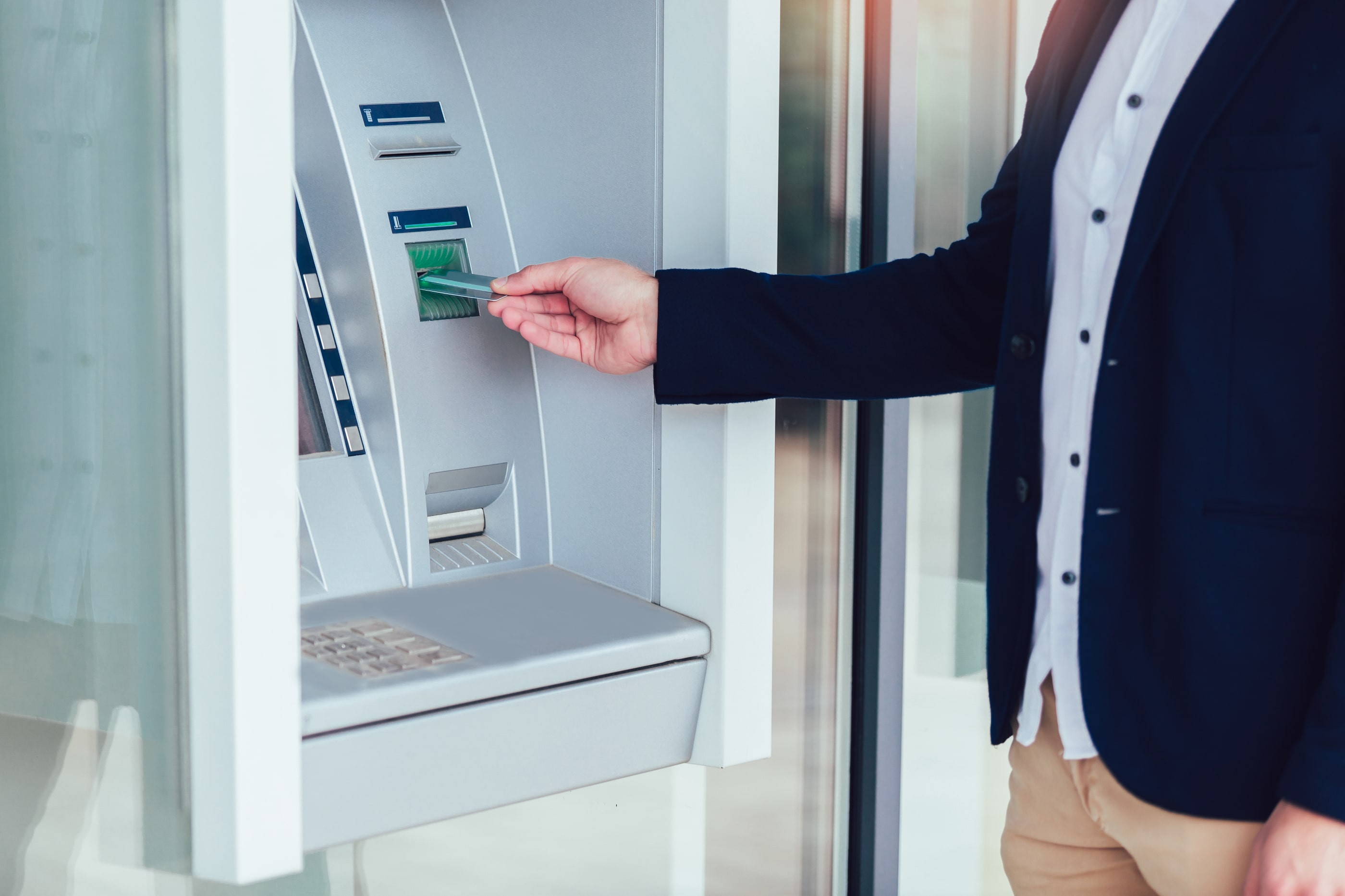 A man inserting his GLCU debit card into a CO-OP atm